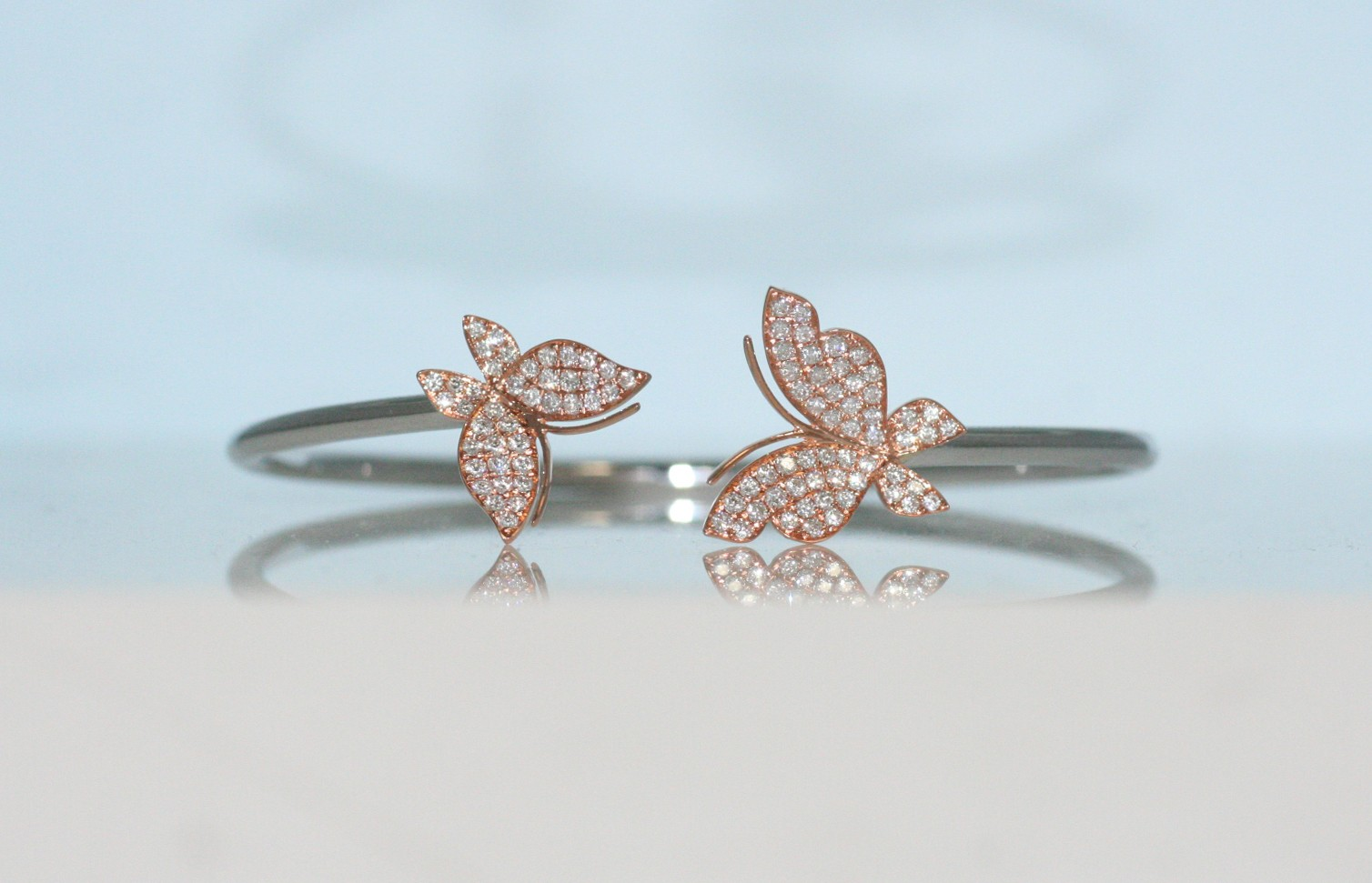 18 karat two tone diamond butterfly bangle.